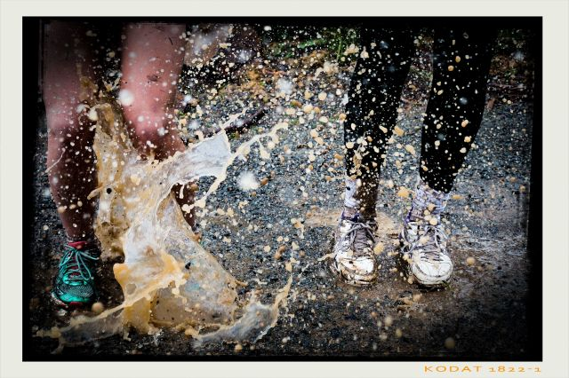mud splashing onto the shoes and legs of two people