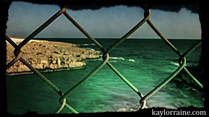 chain link fence separating from sea and shore in the distance