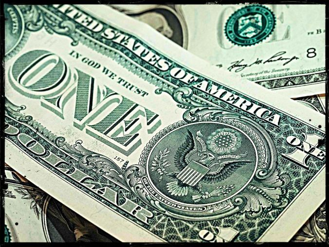 dollar bills lying on top of each other