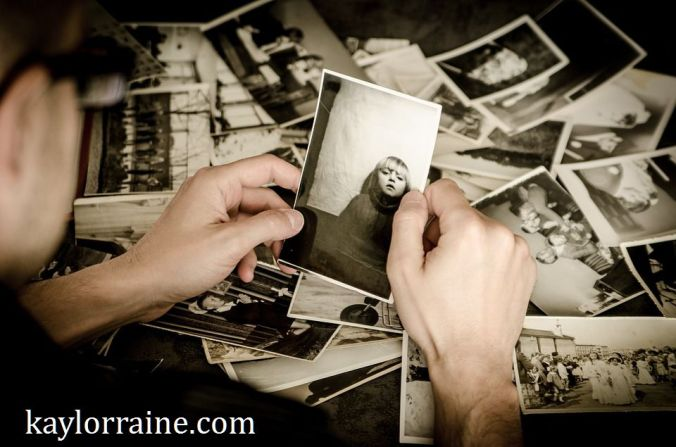 hands holding photograph with many pictures in the background