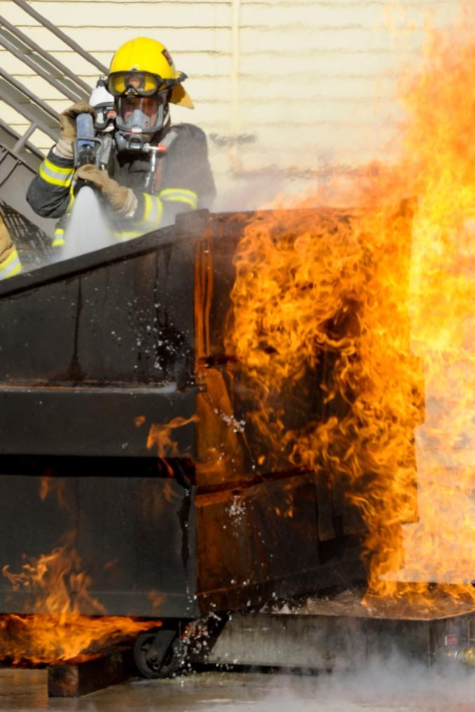 dumpster fire with fireman